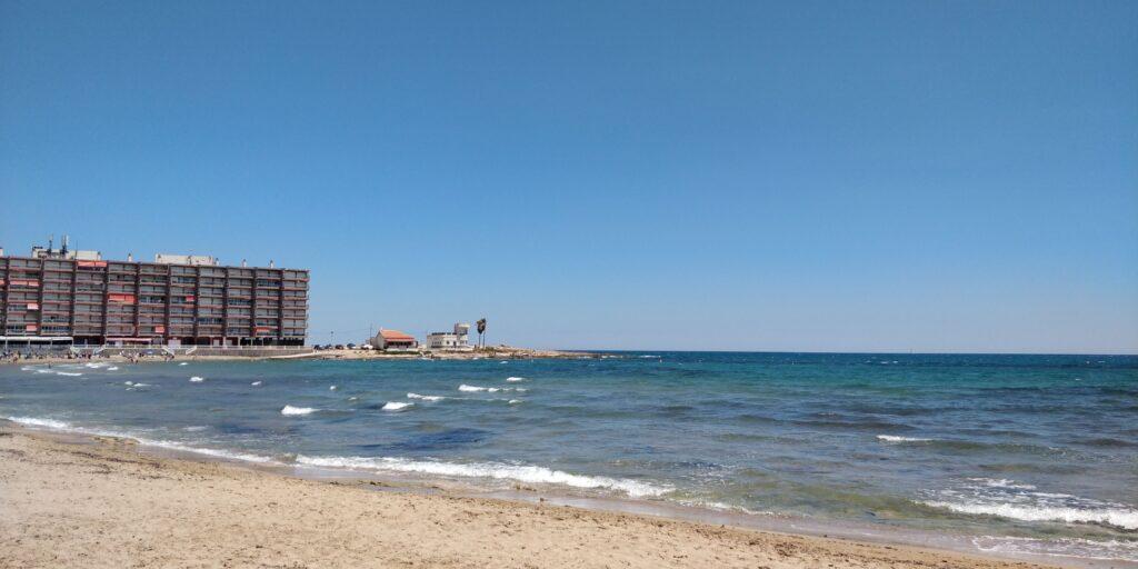 Torrevieja strand på en afslappet dag med bølger i baggrunden