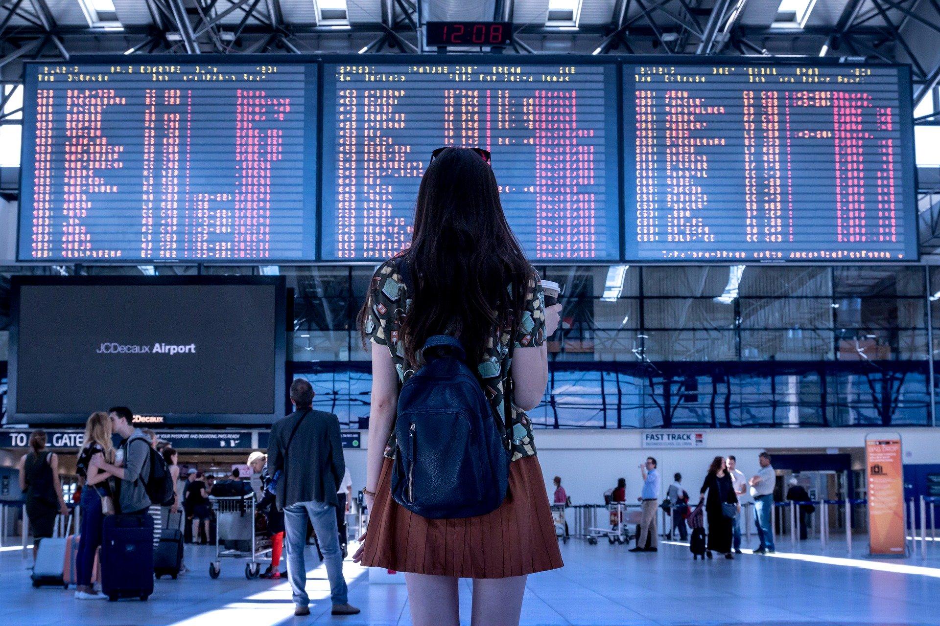 pige der søger efter billige flybilletter til Spanien i en lufthavn | Alt om Spanien